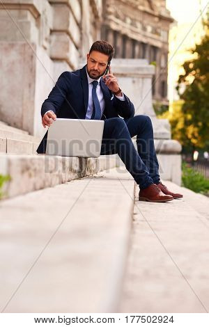 A serious handsome young businessman sitting on the stairs while talking on his phone and using his laptop