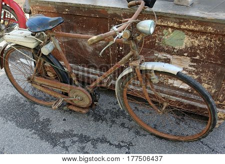Old rusty bicycle moped with motor engine and the gasoline tank