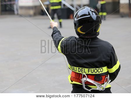 Italian Firefighter With Protective Helmet And A Rope And The Wo
