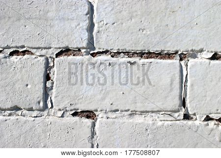 Horizontal design element closeup view of a painted brick wall lit by natural sunlight in an exterior environment.