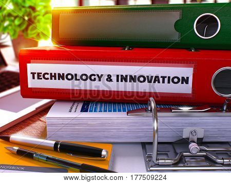 Red Ring Binder with Inscription Technology and Innovation on Blurred Background of Working Table with Office Supplies and Laptop. 3D Render.