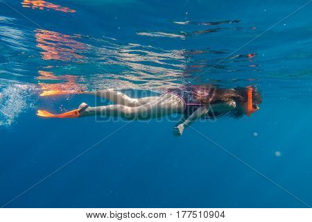 Girl in orange swimming mask and flippers dive in deep sea, underwater shoot