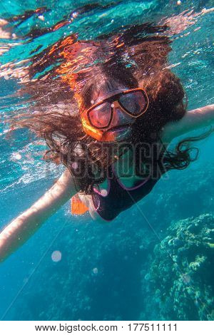 Girl in swimming mask diving in Red sea near coral reef