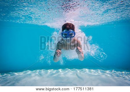 Boy dive in swimming pool, underwater shoot