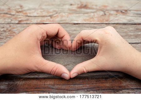 hands of lovers in the shape of hart on wooden background