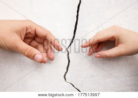 Hands stretching towards each other from otherside of crack of the wall