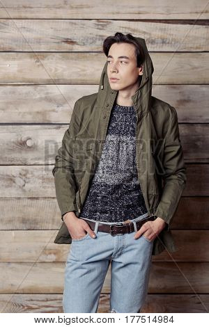 Handsome man wearing green jaket and torn jeans in wooden rural house interior
