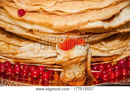 Pancakes with red salmon caviar and fresh berries of redcurrant
