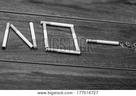 Cigarettes lying on wooden surface shaped into the word no, artistic anti smoking concept, black and white edition.