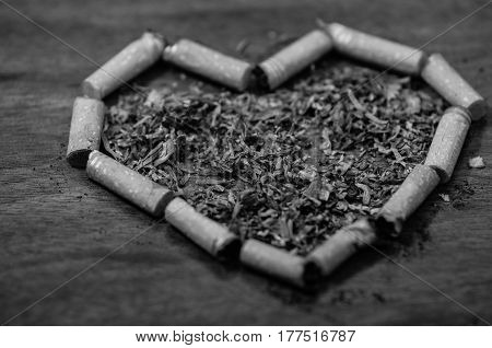 Cigarette butts shaped into a heart lying on wooden surface, tobacco spread around middle, seen from above, black and white edition.