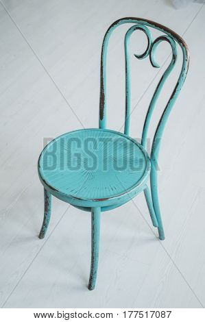 Vintage dirty wooden green elegant chair on a white floor