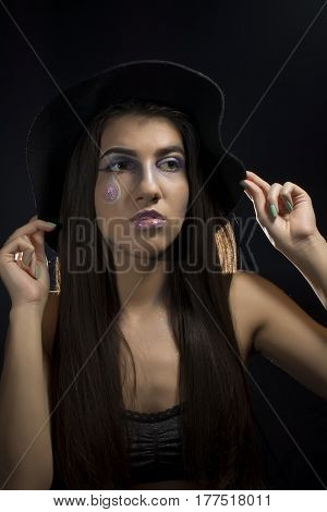 Young girl with  make up wearing black hat
