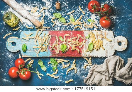 Ingredients for cooking Italian dinner. Fresh pasta casarecce, cherry-tomatoes, basil leaves and bottle of olive oil on colorful wooden board over dark blue background. Top view, horizontal composition