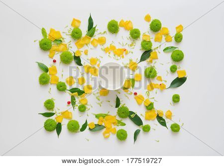 Cup for coffee or tea with pattern with petals of rose flowers, ficus leaves, hearts and ripe rowan on white background. Overhead view. Flat lay.