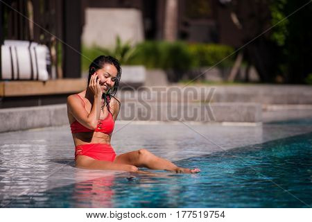 Calling all her friends to join. Portrait of a happy young woman sitting by the pool talking on her phone laughing joyfully.