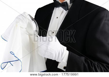 Closeup of a waiter wearing a tuxedo polishing a wineglass. Horizontal format on white. Man is unrecognizable.