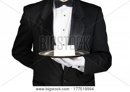 A butler wearing a tuxedo holding a note card on a silver tray in front of his torso. Man is unrecognizable over White.