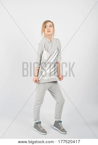 Young hipster girl wearing grey casual clothes and sneakers posing isolated on white background