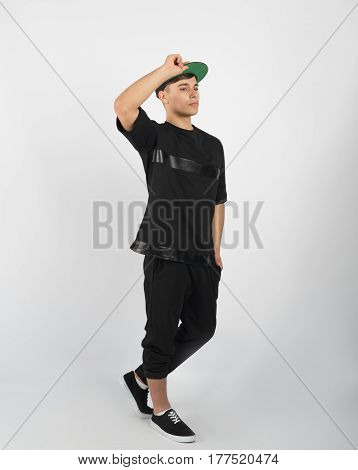 Young muscular man wearing black clothes and sneakers isolated on white background. He is holding his snapback