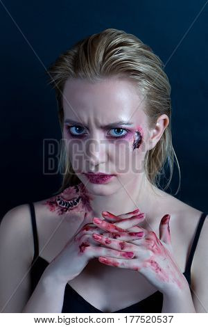 A young blonde girl with blue eyes with a scar on her cheek and a bite on her shoulder. Her hands are in blood. Dark blue background
