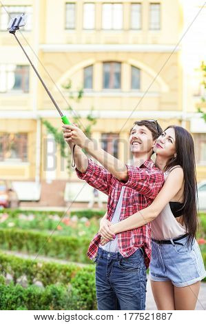 happy young tourists couple taking a selfie with smartphone on the monopod in city. The man is holding the stick and shooting looking at phone with happiness..
