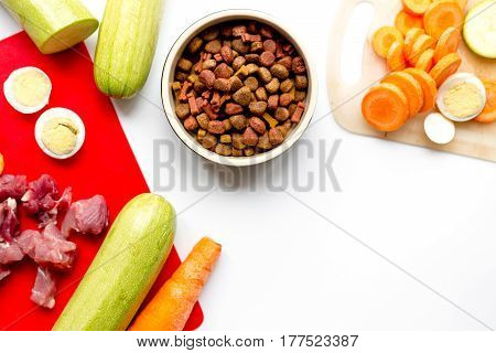 Dogfood set with fresh vegetables, eggs and raw meat on white table background top view mock-up