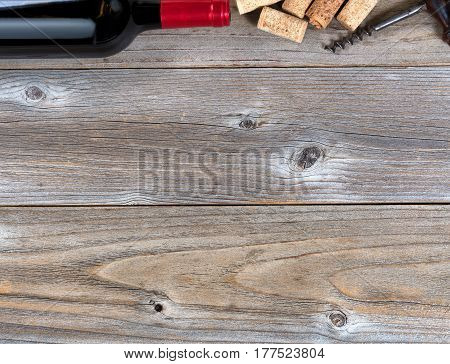 Overhead view of a top border of partial red wine bottle corks and vintage corkscrew on rustic wood