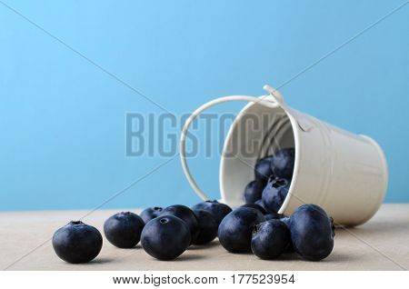 Bucket Of Blueberries Spilling On To Wooden Table With Light Blue Background
