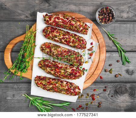 Not cooked meat lula kebab cutlets with vegetable breaded. Not cooked meat lula kebab cutlets with vegetable breaded peppers and tomatoes. Seasonings for meat lula kebab cutlets rosemary thyme and pepper Dried vegetables. Gray rustic wooden background. To