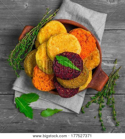 Vegetables patties (cutlets) for vegan burgers in bowl. Mix Vegetables stack fresh burgers. Spices for patties (cutlets) thyme arugula. Gray wooden background. Top view from above and copy space