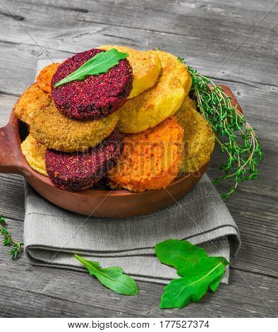 Vegetables patties (cutlets) for vegan burgers in bowl. Mix Vegetables stack fresh burgers. Spices for patties (cutlets) thyme arugula. Gray wooden background.
