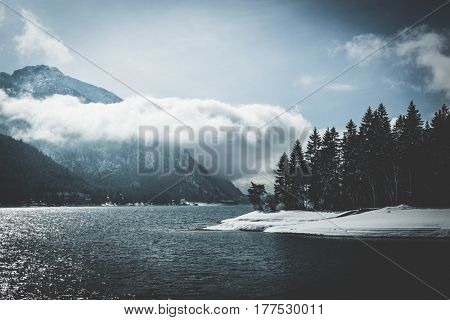 Mountain lake surrounded by pine forest with winter snow and low lying cloud formations clinging to the high alpine mountain peaks in a scenic seasonal landscape