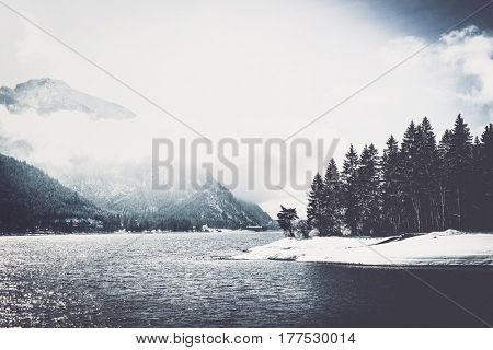 Winter lake with snowy forested banks and low cloud cover clinging to a high alpine mountain peak in a scenic landscape