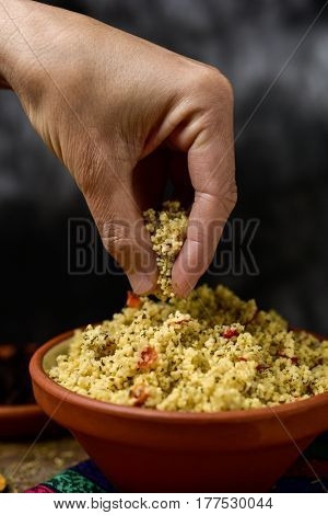 closeup of a young man getting some tabbouleh, a typical levantine arab salad, with his hand from an earthenware bowl placed on a table set for lunch or dinner