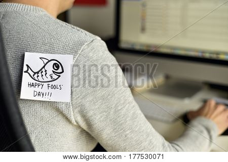 closeup of a young caucasian man seen from behind sitting to his office desk, with a note with a fish and the text happy fools day attached with tape to his back