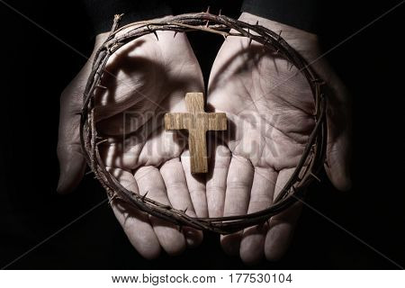 closeup of the hands of a young caucasian man with a small wooden cross and a crown of thorns