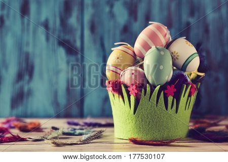 a pile of different decorated easter eggs in a basket decorated as grass and feathers of different colors sprinkled on a rustic surface, against a blue rustic wooden background