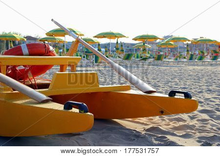 Travel To Rimini, Italy. The Catamaran On The Foreground On The Empty Beach With A Lot Of Sunbeds An