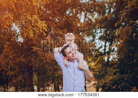 Dad with his little daughter sitting on a white plaid in the summer park