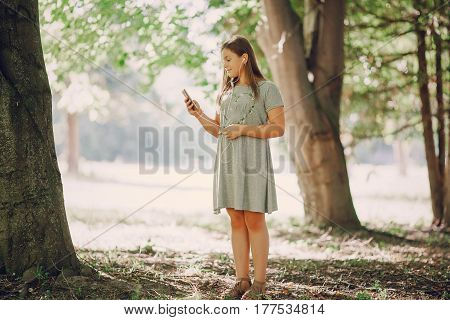 girl standing in a forest near trees and holds phone