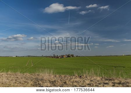 Green spring field with small village Hlinoviste and blue sky