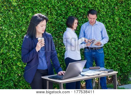 Businesswoman working outside office with team at green leaf wallbusiness on go and using digital technology device to corporate workflow.