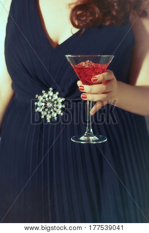 Young woman wearing a party dress holding a cocktail