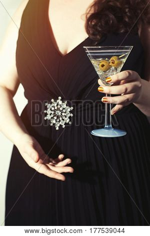 Young woman in party dress holding a Martini cocktail
