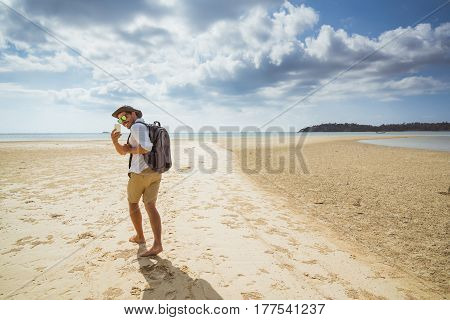 hiker walking forward in the sandy desert turning around making a photo on his mobile phone smartphone. travel carrying one's belongings in a backpack.