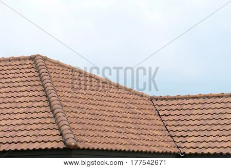 Roof house with tiled roof on blue sky. orange Roof house.