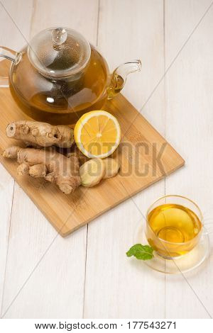 Cup Of Ginger Tea With Lemon And Honey On White Wooden Background.