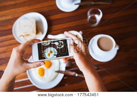 Girl blogger food photographer takes photo food on her phone smartphone. Breakfast of two fried eggs coffee and oatmeal with milk