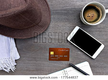 Mobile smart phone credit card notebook hat mad of fabric and a cup of coffee on wood texture background.