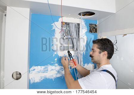 Electrician wearing overalls installing distribution board.